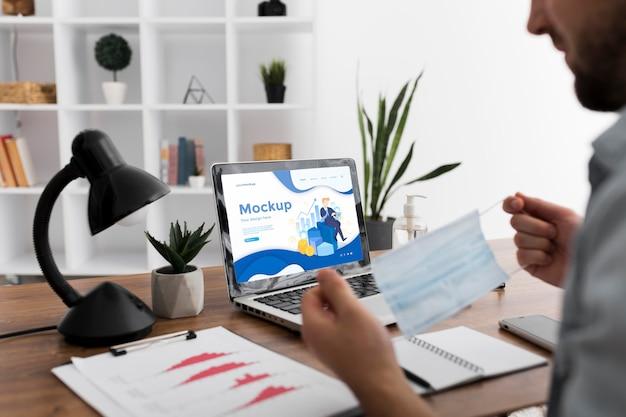 Homme au bureau avec masque et maquette d'ordinateur portable