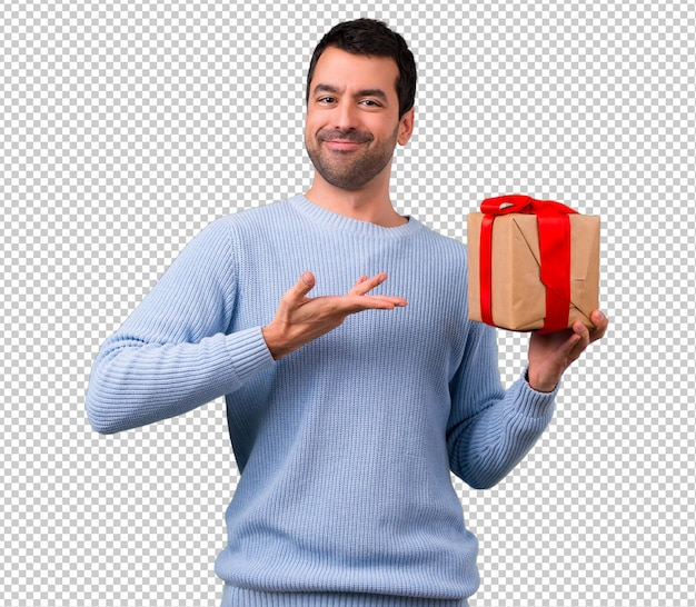 Homme au pull bleu tenant des boîtes-cadeaux dans les mains