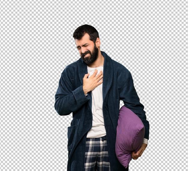 Homme à la barbe en pyjama ayant une douleur au coeur