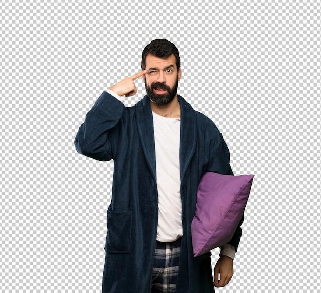 Homme à la barbe en pyjama faisant le geste de la folie mettant le doigt sur la tête