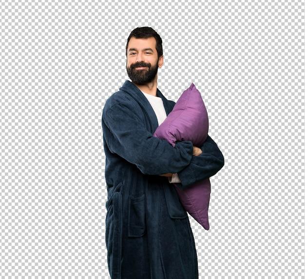 Homme à la barbe en pyjama en gardant les bras croisés en position frontale