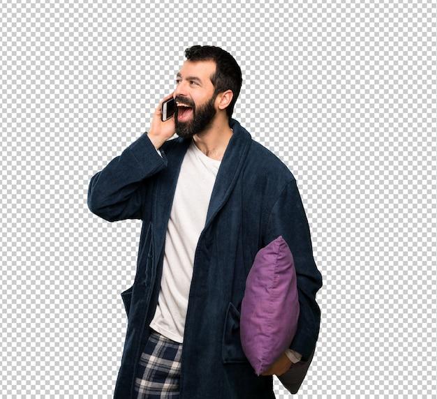 Homme à la barbe en pyjama gardant une conversation avec le téléphone portable
