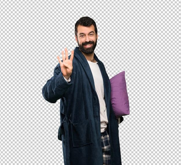 Homme à la barbe en pyjama heureux et comptant quatre avec les doigts