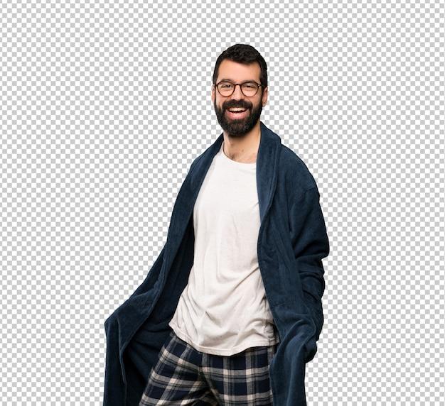 Homme à la barbe en pyjama avec des lunettes et souriant