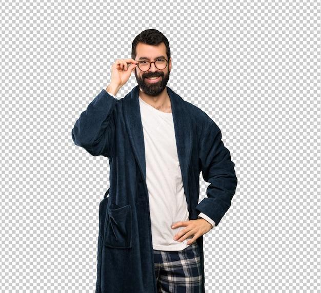 Homme à la barbe en pyjama avec des lunettes et surpris