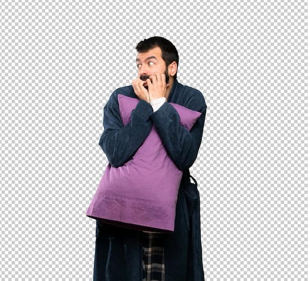 Homme à la barbe en pyjama nerveux et effrayé mettant les mains à la bouche