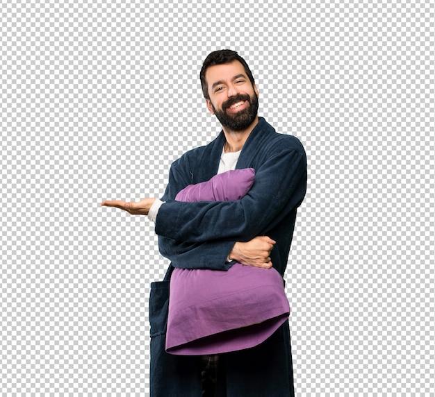 Homme à la barbe en pyjama présentant une idée tout en regardant en souriant