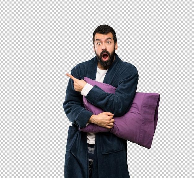 Homme à la barbe en pyjama surpris et pointant le côté