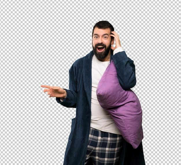 Homme à la barbe en pyjama surpris et pointant du doigt sur le côté
