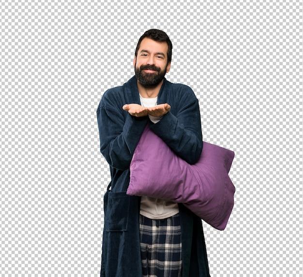 Homme à la barbe en pyjama tenant une surface imaginaire sur la paume pour insérer une annonce