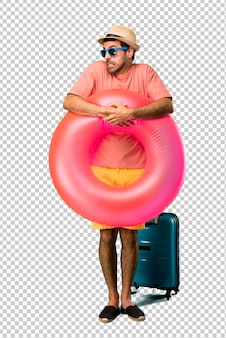 Un homme avec un chapeau et des lunettes de soleil pendant ses vacances d'été est un peu nerveux et a peur d'appuyer sur ses dents
