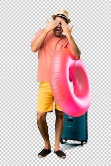 Homme avec chapeau et des lunettes de soleil sur ses vacances d'été, couvrant les yeux par les mains. surpris de voir ce qui nous attend