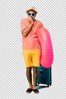 Homme avec chapeau et lunettes de soleil sur ses vacances d'été est un peu nerveux et peureux de mettre ses mains à la bouche