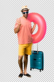 Homme avec chapeau et des lunettes de soleil sur ses vacances d'été heureux et comptant avec trois doigts