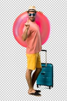 Homme avec chapeau et lunettes de soleil sur ses vacances d'été montrant et en levant un doigt en signe du meilleur
