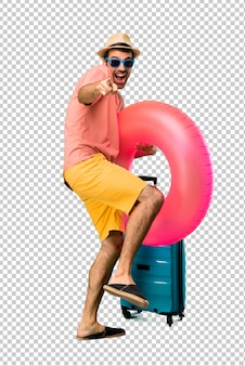 Homme avec chapeau et lunettes de soleil sur ses vacances d'été pointant du doigt quelqu'un et riant beaucoup
