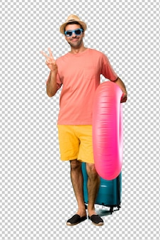 Homme avec chapeau et lunettes de soleil sur ses vacances d'été souriant et montrant le signe de la victoire avec un visage joyeux