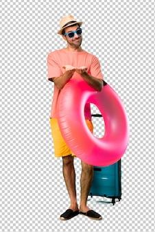 Homme avec chapeau et lunettes de soleil sur ses vacances d'été, tenant une surface imaginaire sur la paume pour insérer une annonce
