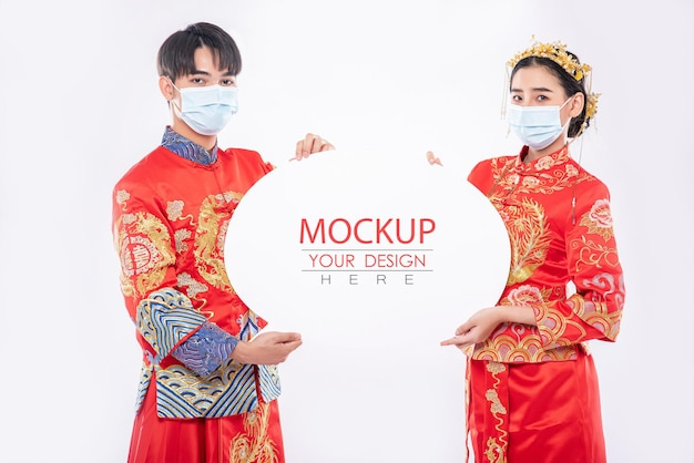 Homme chinois et femme chinoise tiennent une maquette de bulle de dialogue vierge