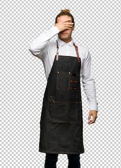 Homme de coiffeur dans un tablier couvrant les yeux à la main. je ne veux pas voir quelque chose