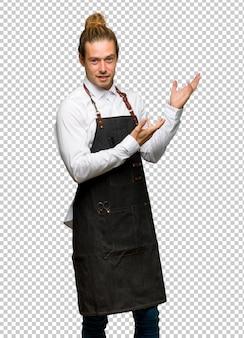Homme de coiffeur dans un tablier tendant les mains sur le côté pour avoir invité à venir