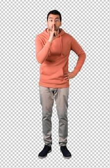 Homme dans un sweat-shirt rose montrant un signe de fermeture de la bouche et un geste de silence mettant un doigt dans la bouche