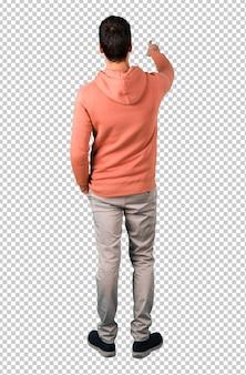 Homme dans un sweat-shirt rose pointant vers l'arrière avec l'index présentant un produit par derrière