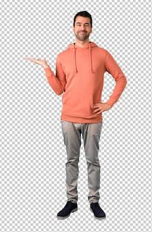 Homme dans un sweat-shirt rose tenant un espace de copie imaginaire sur la paume pour insérer une annonce