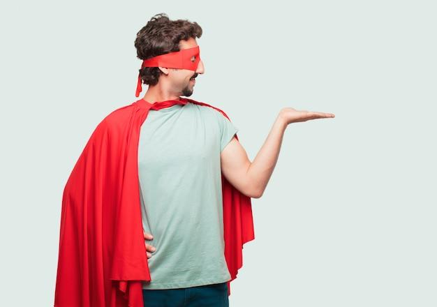 Homme fou comme un super héros souriant avec une expression satisfaite montrant un objet ou un concept