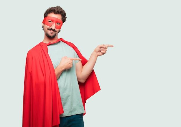 Homme fou comme un super héros souriant et pointant du côté des deux mains