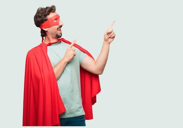 Homme fou comme un super héros souriant et pointant vers le haut avec les deux mains