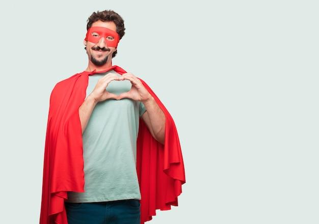Homme fou comme un super héros souriant, regardant heureux et amoureux, faisant la forme d'un coeur avec les mains