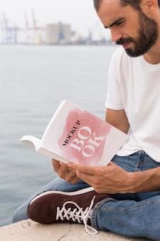 Homme sur livre de lecture de rue
