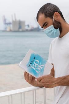 Homme avec masque sur livre de lecture de rue