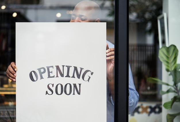Homme mettant en ouverture de magasin bientôt signer