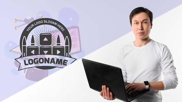 Homme avec montre tenant un ordinateur portable