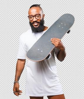 Homme noir tenant une planche à roulettes