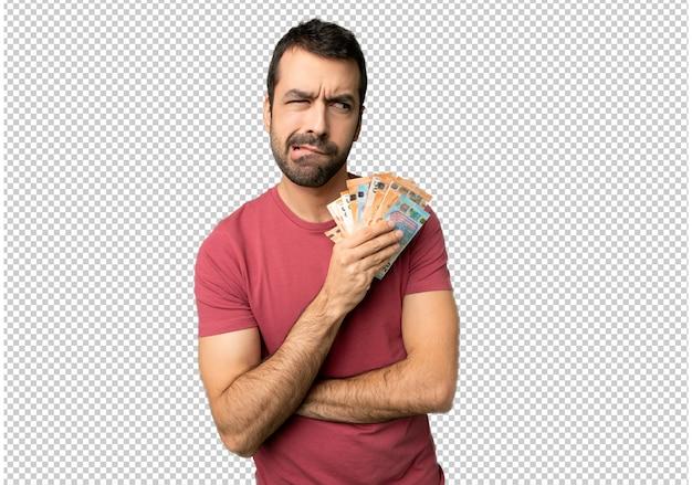 Homme prenant beaucoup d'argent avec une expression de visage confuse tandis que ses lèvres mordent