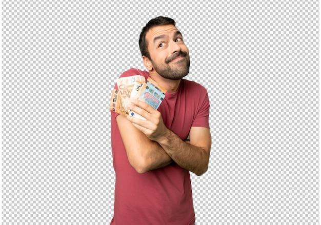 Homme prenant beaucoup d'argent en faisant des gestes de doutes tout en soulevant les épaules