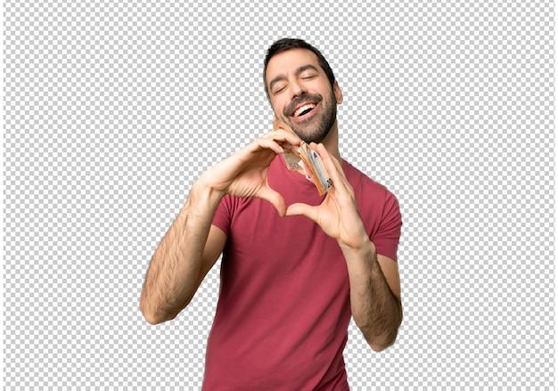 Homme prenant beaucoup d'argent faisant le symbole du coeur à la main