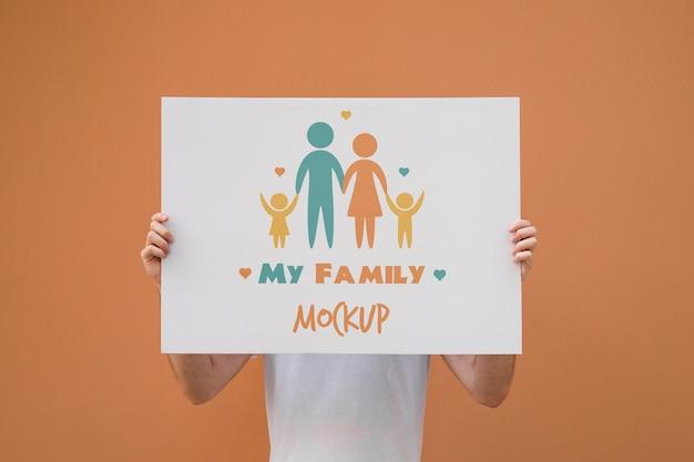 Homme présentant une maquette d'affiche sur fond orange