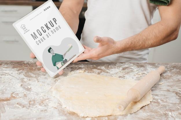 Homme roulant la pâte dans la cuisine et tenant le livre