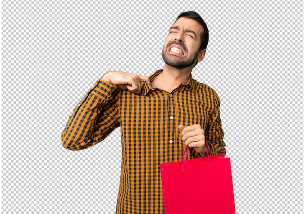 Homme avec des sacs à provisions avec expression fatiguée et malade