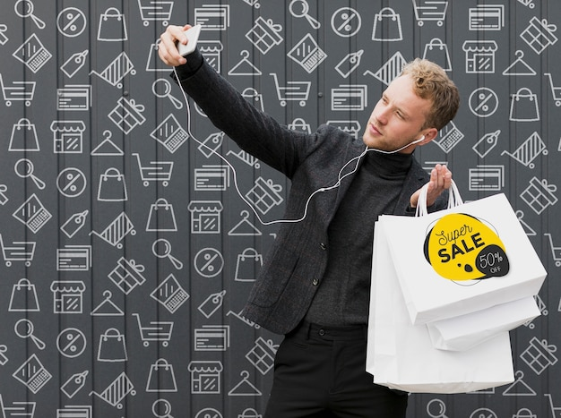 Homme souriant prenant selfie avec ses courses