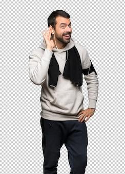 Homme de sport écoute quelque chose en mettant la main sur l'oreille