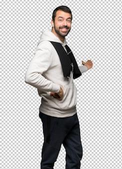 Homme de sport pointant en arrière et présentant un produit