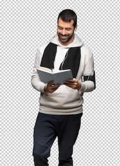 Homme de sport tenant un livre et profiter de la lecture