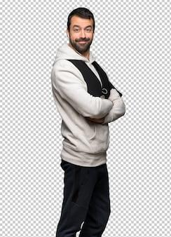 Homme sportif gardant les bras croisés en position latérale tout en souriant