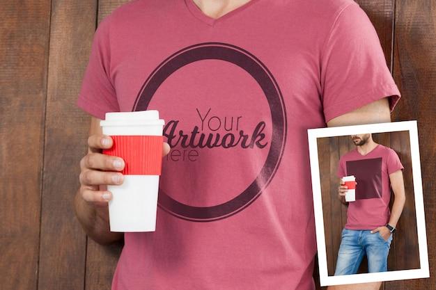Homme en t-shirt rose tenant une tasse de café jetable