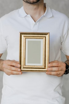 Homme tenant une maquette de cadre doré